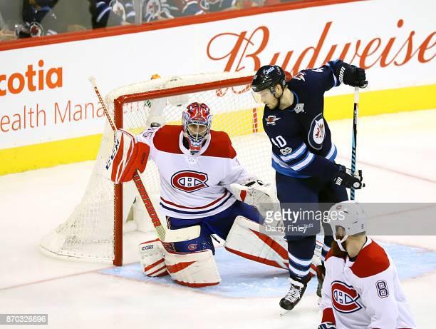 Joel Armia of the Winnipeg Jets watches as a shot by teammate Nikolaj Ehlers flies over the shoulder of goaltender Al Montoya of the Montreal...