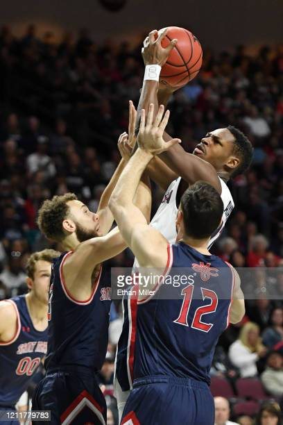 Joel Ayayi of the Gonzaga Bulldogs shoots against Jordan Ford and Tommy Kuhse of the Saint Mary's Gaels during the championship game of the West...