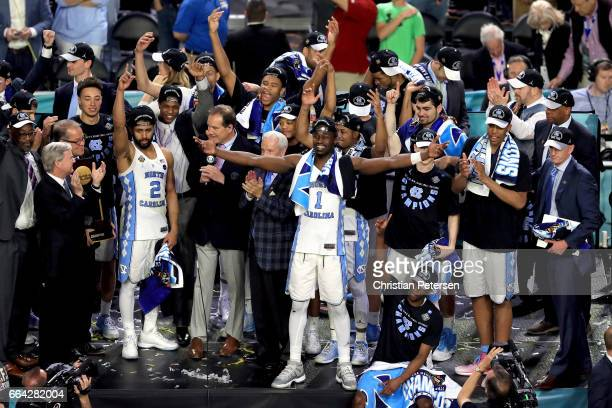 Joel Berry II and Theo Pinson of the North Carolina Tar Heels celebrate with head coach Roy Williams and their team after defeating the Gonzaga...