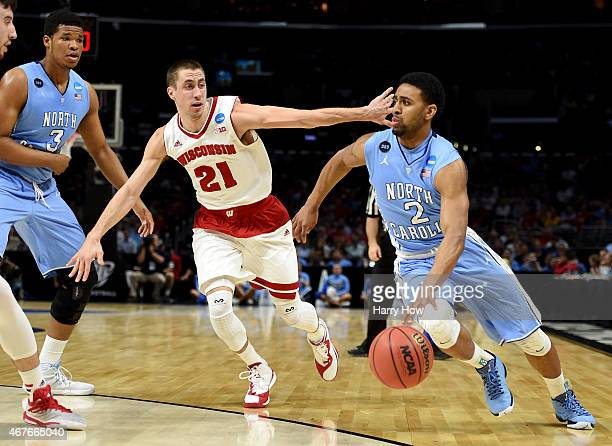 Joel Berry II of the North Carolina Tar Heels drives on Josh Gasser of the Wisconsin Badgers in the first half during the West Regional Semifinal of...