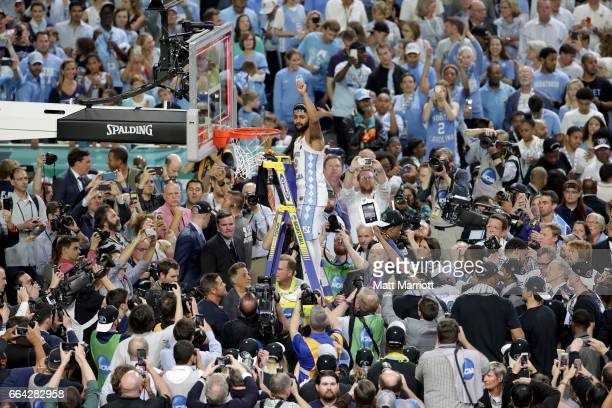 Joel Berry II of the North Carolina Tar Heels raises a piece of the net following the 2017 NCAA Men's Final Four National Championship game against...