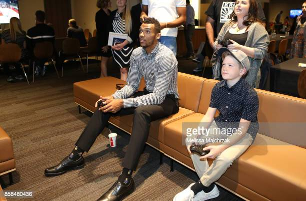 Joel Bolomboy of the Utah Jazz plays video games with a young fan during Game Night with the Jazz at vivintSmartHome Arena on October 05 2017 in Salt...
