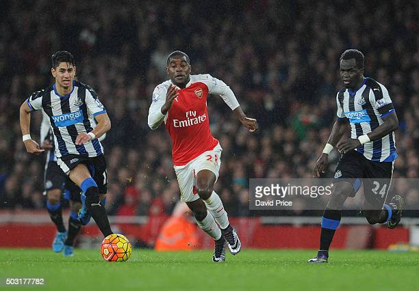 Joel Campbell of Arsenal takes on Cheick Tiote and Ayoze Perez of Newcastle during the Barclays Premier League match between Arsenal and Newcastle...
