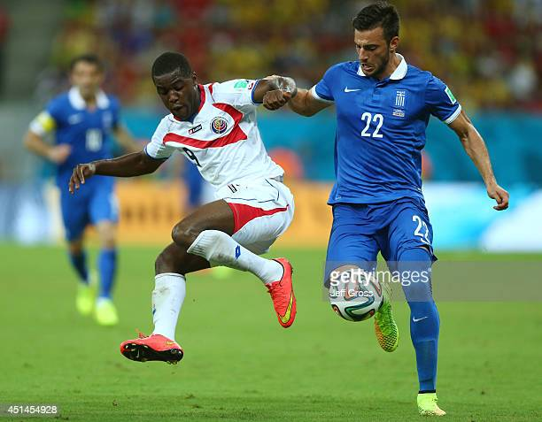 Joel Campbell of Costa Rica and Andreas Samaris of Greece compete for the ball during the 2014 FIFA World Cup Brazil Round of 16 match between Costa...