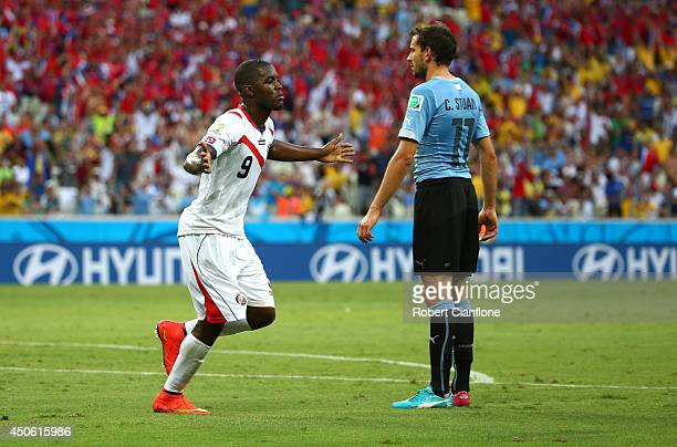 Joel Campbell of Costa Rica celebrates scoring his team's first goal as Christian Stuani of Uruguay looks on during the 2014 FIFA World Cup Brazil...