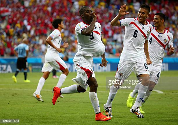 Joel Campbell of Costa Rica celebrates scoring his team's first goal with the ball under his jersey as teammates Oscar Duarte and Michael Umana run...