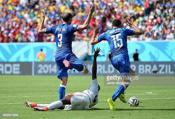 Joel Campbell of Costa Rica falls after a challenge by Giorgio Chiellini and Andrea Barzagli of Italy during the 2014 FIFA World Cup Brazil Group D...