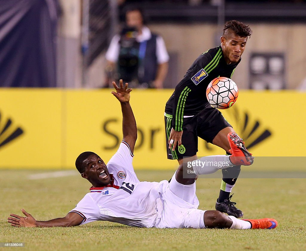 Joel Campbell #12 of Costa Rica falls as Jonathan do Santos #8 of Mexico tries to make the steal during the quarterfinals of the 2015 CONCACAF Gold Cup at MetLife Stadium on July 19, 2015 in East Rutherford, New Jersey.