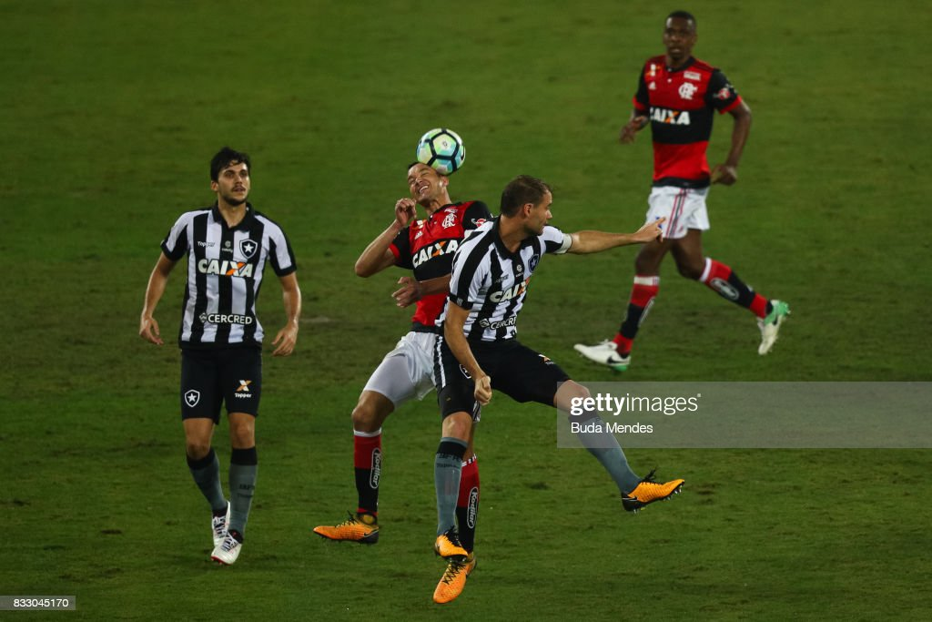 Joel Carli (C) of Botafogo struggles for the ball with Rever of Flamengo during a match between Botafogo and Flamengo as part of Copa do Brasil Semifinals 2017 at Nilton Santos Olympic Stadium on August 16, 2017 in Rio de Janeiro, Brazil.