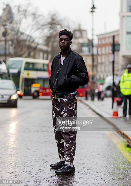 Joel Claudio wearin a black bomber jacket camouflage pantsduring London Fashion Week Men's January 2017 collections at Katy Eary on January 7 2017 in...
