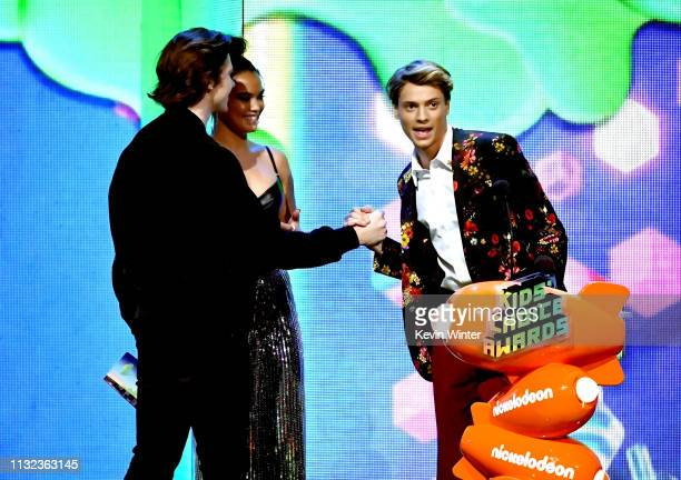 Joel Courtney and Paris Berelc present Jace Norman with the Favorite Male TV Staraward for 'Henry Danger' onstage at Nickelodeon's 2019 Kids' Choice...