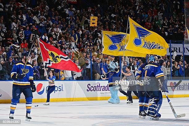 Joel Edmundson David Backes and Brian Elliott of the St Louis Blues salute the fans as the ice crew skates with flags after defeating the Chicago...