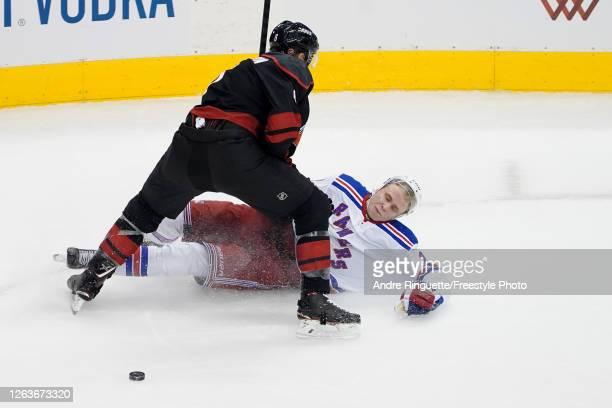 Joel Edmundson of the Carolina Hurricanes knocks Kaapo Kakko of the New York Rangers to the ground during the second period of Game Two of the...