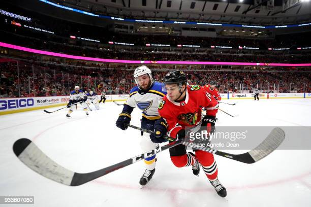 Joel Edmundson of the St Louis Blues and Alex DeBrincat of the Chicago Blackhawks get physical in the second period at the United Center on March 18...