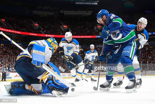 Joel Edmundson of the St Louis Blues and Sam Gagner of the Vancouver Canucks look on as Jake Allen of the St Louis Blues makes a save during their...