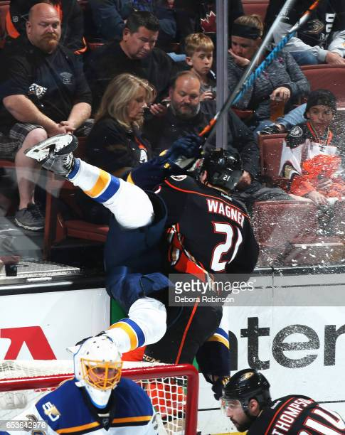 Joel Edmundson of the St Louis Blues gets checked by Chris Wagner of the Anaheim Ducks during the game on March 15 2017 at Honda Center in Anaheim...