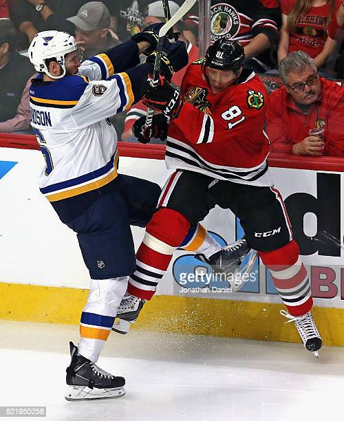 Joel Edmundson of the St Louis Blues hits Marian Hossa of the Chicago Blackhawks in Game Three of the Western Conference Quarterfinals during the...
