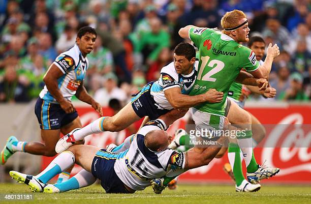 Joel Edwards of the Raiders is tackled by Matthew White and Mark Minichiello of the Titans during the round three NRL match between the Canberra...