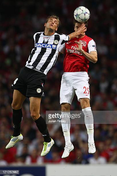 Joel Ekstrand of Udinese hits Carl Jenkinson of Arsenal in the face as they both jump for the ball during the UEFA Champions League play-off first...