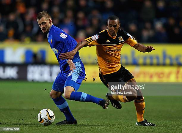 Joel Ekstrand of Watford and Jay Simpson of Hull City challenge for the ball during the npower Championship match between Hull City and Watford at KC...