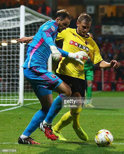 Joel Ekstrand of Watford battles with goalkeeper David Button of Brentford during the Sky Bet Championship match between Watford and Brentford at...