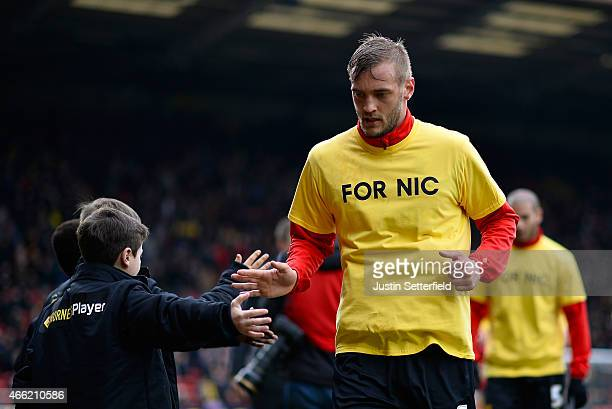Joel Ekstrand of Watford warms up wearing a t-shirt in tribute to critically ill Watford fan Nick Cruwys ahead of the Sky Bet Championship match...