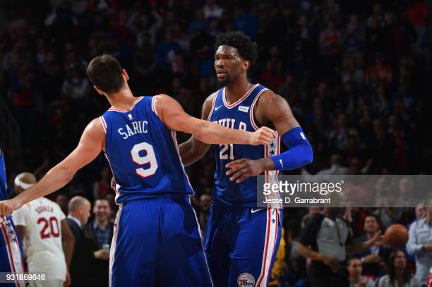 Joel Embiid and Dario Saric of the Philadelphia 76ers chest bump against the Indiana Pacers at the Wells Fargo Center on March 13 2018 in...