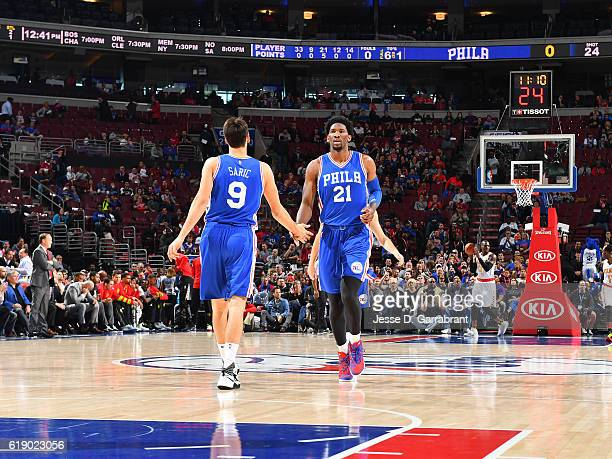 Joel Embiid and Dario Saric of the Philadelphia 76ers shake hands against Atlanta Hawks during a game at the Wells Fargo Center on October 29 2016 in...