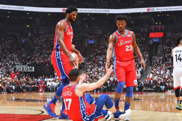 Joel Embiid and Jimmy Butler assist JJ Redick of the Philadelphia 76ers off for the floor against the Toronto Raptors during Game Seven of the...