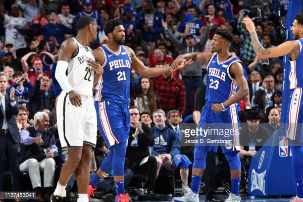 Joel Embiid and Jimmy Butler of the Philadelphia 76ers highfive during a game against the Brooklyn Nets during Game Two of Round One of the 2019 NBA...