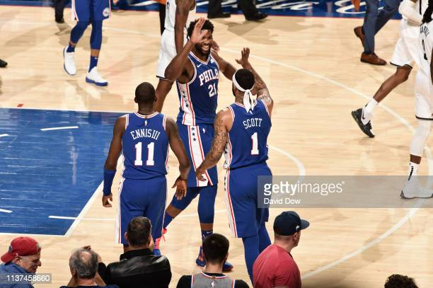 Joel Embiid and Mike Scott of the Philadelphia 76ers high five in Game Two of Round One against the Brooklyn Nets during the 2019 NBA Playoffs on...