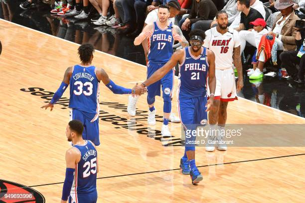Joel Embiid and Robert Covington of the Philadelphia 76ers high five during the game against the Miami Heat in Game Four of Round One of the 2018 NBA...