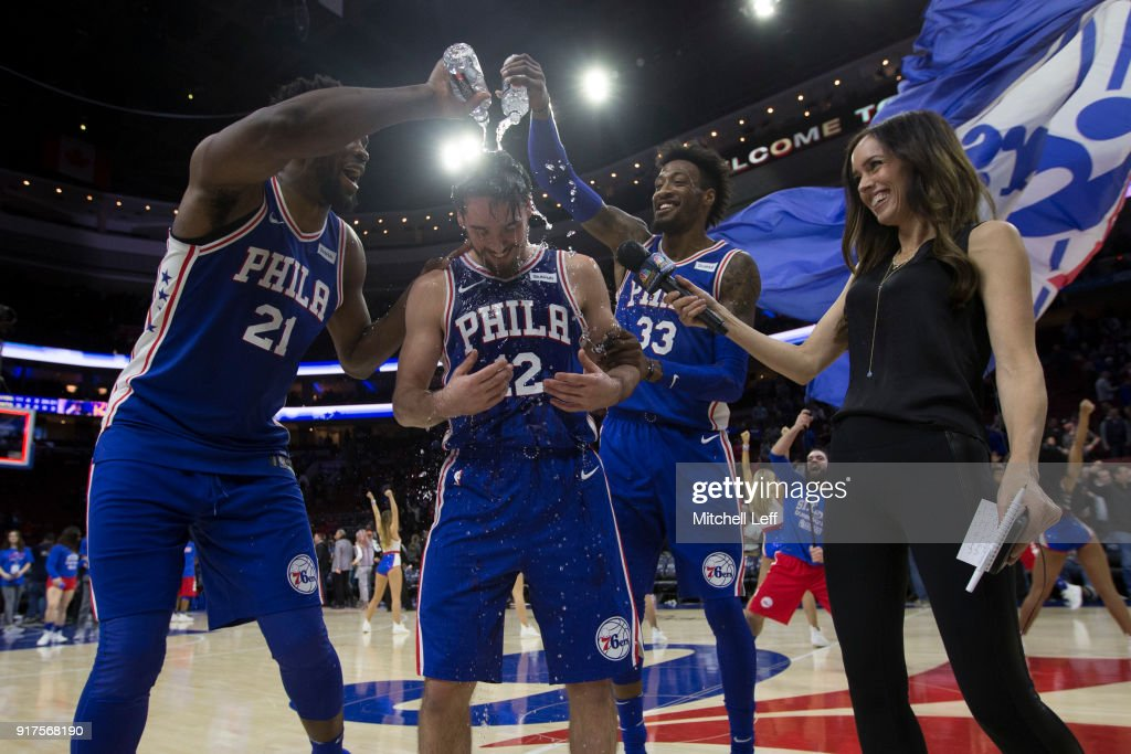 Joel Embiid #21 and Robert Covington #33 of the Philadelphia 76ers pour water on T.J. McConnell #12 after McConnell recorded a triple double against the New York Knicks at the Wells Fargo Center on February 12, 2018 in Philadelphia, Pennsylvania. The 76ers defeated the Knicks 108-92.