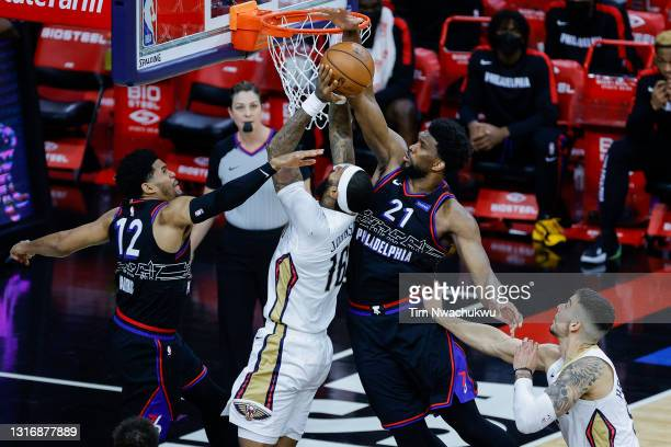 Joel Embiid and Tobias Harris of the Philadelphia 76ers defend the shot attempt by James Johnson of the New Orleans Pelicans during the fourth...