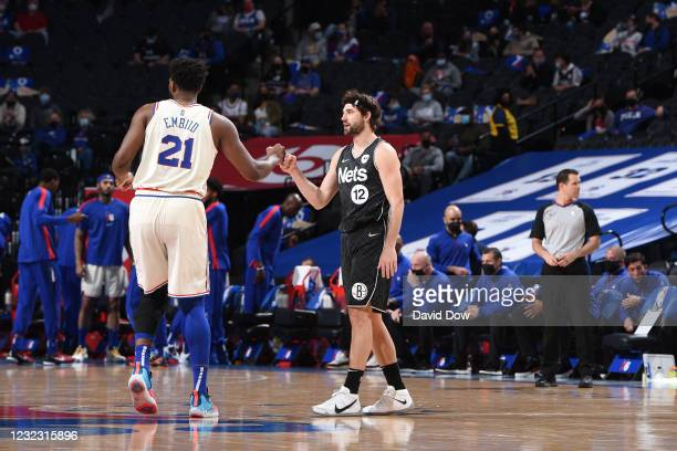 Joel Embiid of the Philadelphia 76ers and Joe Harris of the Brooklyn Nets high-five prior to a game on April 14, 2021 at Wells Fargo Center in...