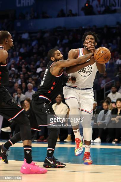 Joel Embiid of the Philadelphia 76ers and Team Giannis is pressed as he drives against Kyrie Irving of the Boston Celtics and Team LeBron the third...