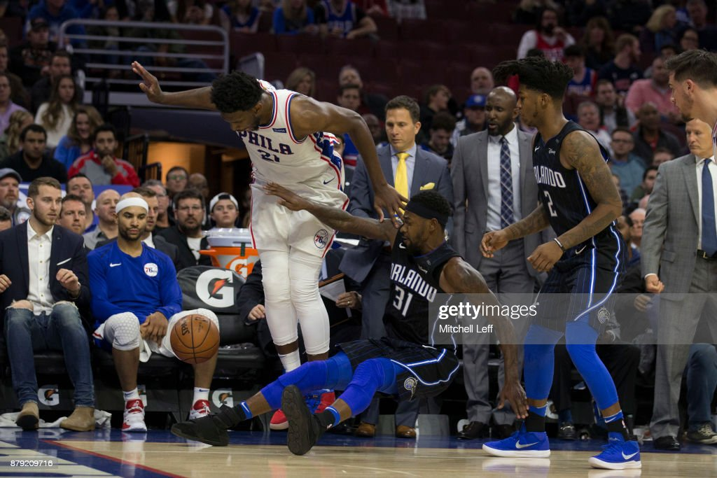 Joel Embiid #21 of the Philadelphia 76ers and Terrence Ross #31 of the Orlando Magic try to avoid touching the ball as it goes out of bounds in the fourth quarter at the Wells Fargo Center on November 25, 2017 in Philadelphia, Pennsylvania. The 76ers defeated the Magic 130-111.