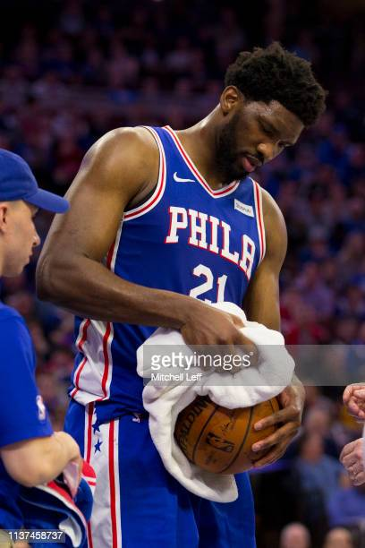 Joel Embiid of the Philadelphia 76ers attempts to dry off the basketball with a towel against the Brooklyn Nets in the fourth quarter of Game Two of...