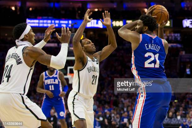 Joel Embiid of the Philadelphia 76ers controls the ball against Rondae HollisJefferson and Treveon Graham of the Brooklyn Nets in Game Two of Round...
