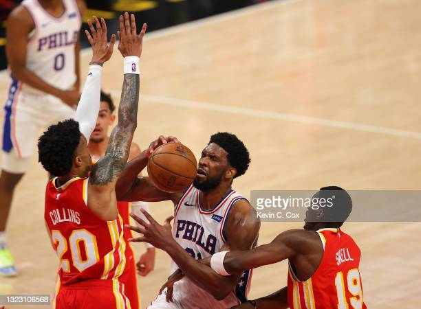 Joel Embiid of the Philadelphia 76ers draws a foul from Tony Snell of the Atlanta Hawks as he drives against John Collins during the first half of...