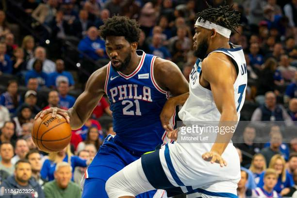 Joel Embiid of the Philadelphia 76ers dribbles the ball against KarlAnthony Towns of the Minnesota Timberwolves at the Wells Fargo Center on October...