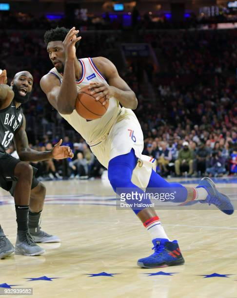 Joel Embiid of the Philadelphia 76ers drives past Quincy Acy of the Brooklyn Nets at the Wells Fargo Center on March 16 2018 in Philadelphia...