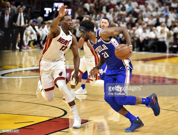 Joel Embiid of the Philadelphia 76ers drives to the basket while being defended by Bam Adebayo of the Miami Heat at American Airlines Arena on April...