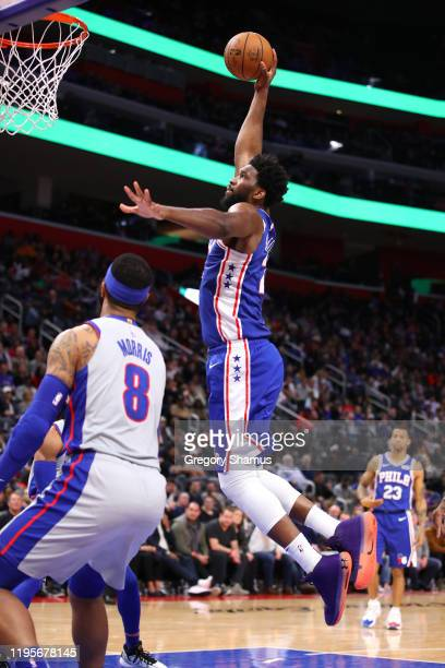 Joel Embiid of the Philadelphia 76ers dunks past Markieff Morris of the Detroit Pistons during the second half at Little Caesars Arena on December 23...