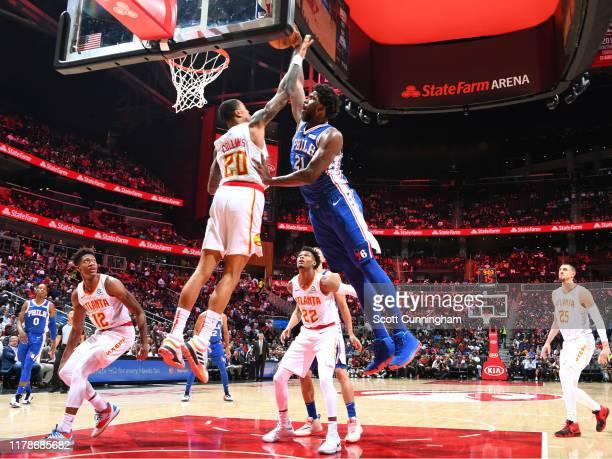 Joel Embiid of the Philadelphia 76ers dunks teh ball against John Collins of the Atlanta Hawks on October 28 2019 at State Farm Arena in Atlanta...