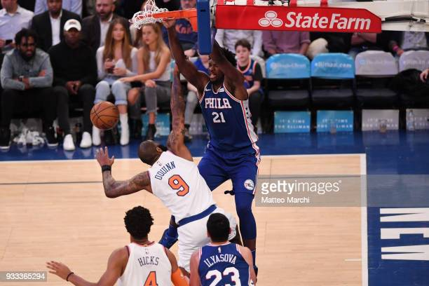 Joel Embiid of the Philadelphia 76ers dunks the ball against Kyle O'Quinn of the New York Knicks during the game at Madison Square Garden on March 15...