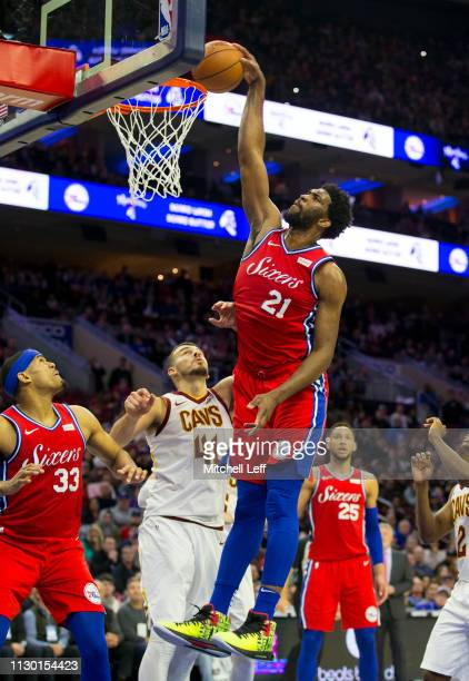 Joel Embiid of the Philadelphia 76ers dunks the ball past Ante Zizic of the Cleveland Cavaliers in the fourth quarter at the Wells Fargo Center on...