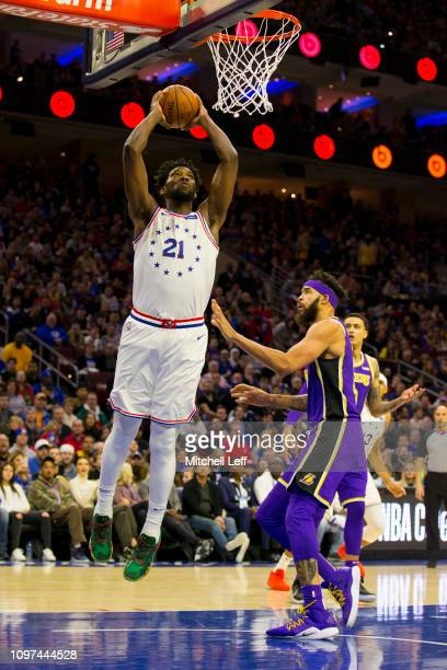 Joel Embiid of the Philadelphia 76ers dunks the ball past JaVale McGee of the Los Angeles Lakers in the first quarter at the Wells Fargo Center on...
