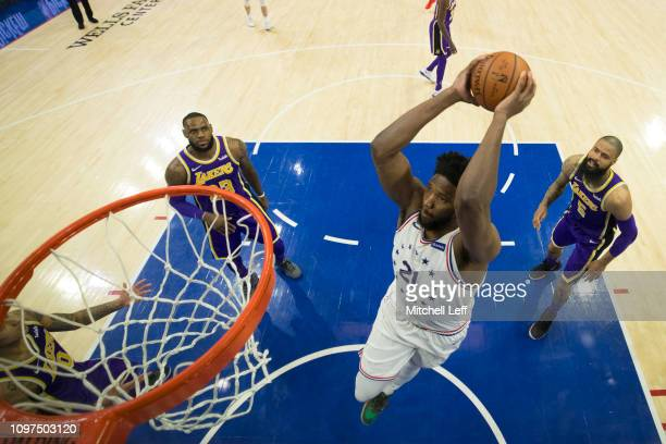 Joel Embiid of the Philadelphia 76ers dunks the ball past LeBron James and Tyson Chandler of the Los Angeles Lakers in the second quarter at the...