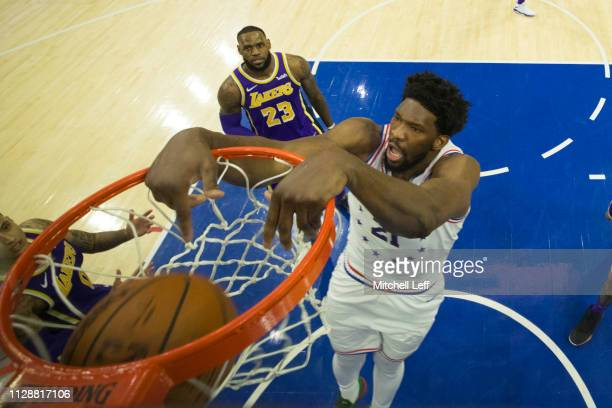 Joel Embiid of the Philadelphia 76ers dunks the ball past LeBron James of the Los Angeles Lakers at the Wells Fargo Center on February 10 2019 in...